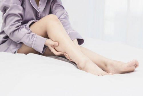 Une femme se masse la jambe