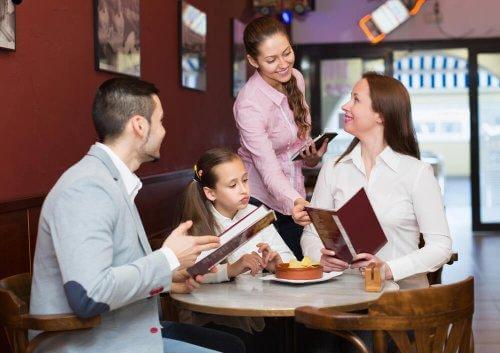 Des parents et leur fille sont au restaurant