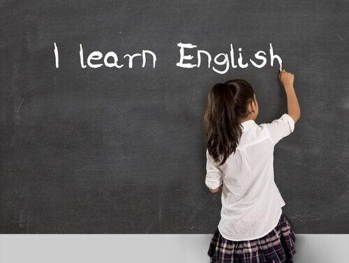 Une fille écrit en anglais au tableau