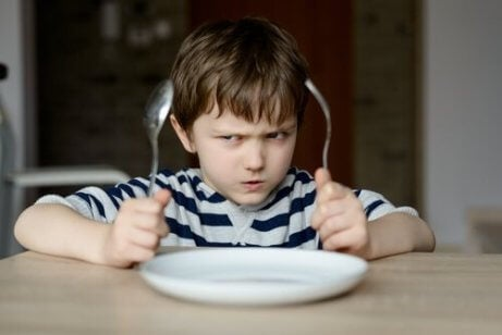 Un enfant va manger avec des couverts