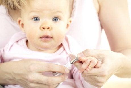Un bébé se fait couper les ongles