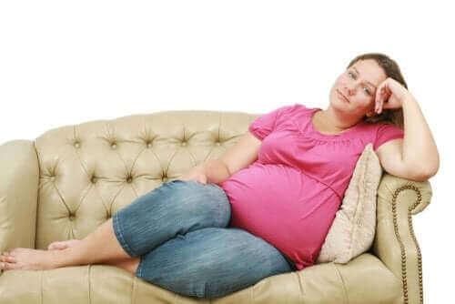 Une femme enceinte sur un sofa.