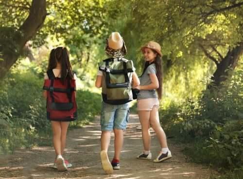 Enfants qui marchent sur un chemin avec de petits sacs à dos