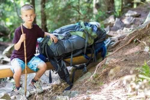 Enfant qui pose à côté d'un gros sac à dos de randonnée en forêt