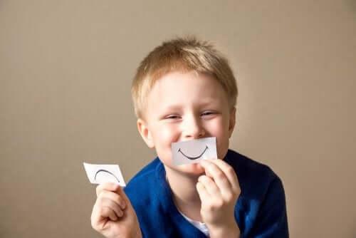 Enfant avec un sourire en papier devant la bouche
