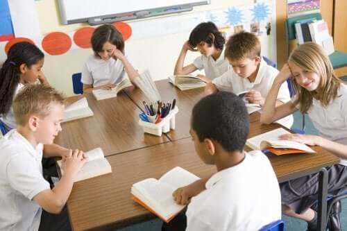 Des enfants qui lisent un livre dans une salle de classe.