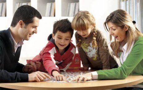 Des parents qui jouent à un jeu de société avec leurs enfants