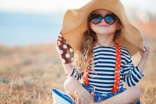Petite fille qui porte un grand chapeau et des lunettes