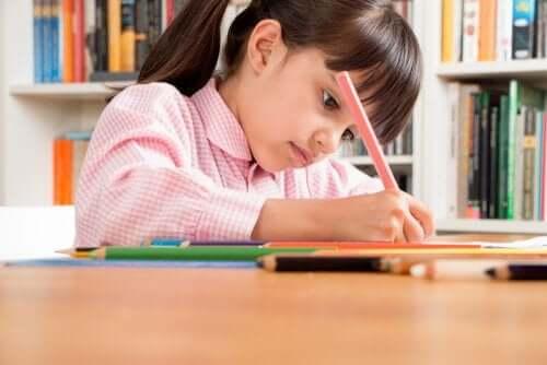Une petite fille qui écrit dans un cahier.