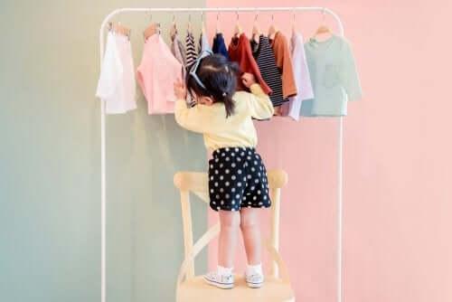 Petite fille qui choisit des vêtements