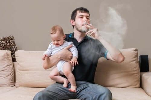 père fumant une cigarette avec son bébé