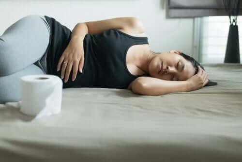 femme allongée sur le côté face à du papier toilette