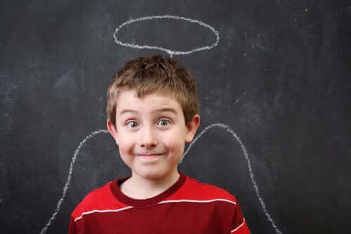 enfant devant un tableau noir avec un dessin d'ange