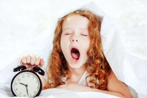 fille au lit avec son réveil