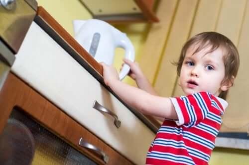 enfant prenant une bouilloire