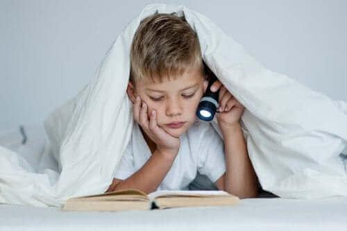 enfant étudiant dans son lit