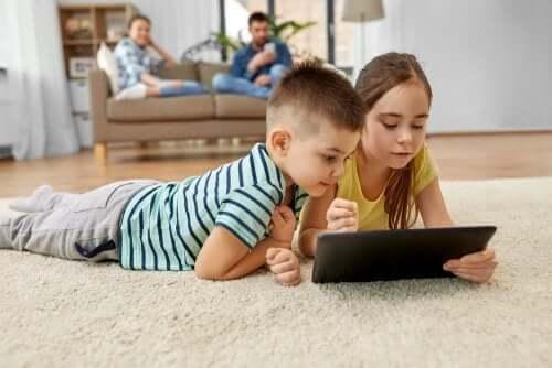 enfants devant leur tablette dans le salon avec leurs parents