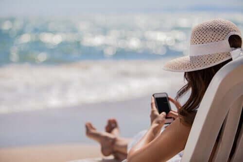 femme à la plage avec son téléphone