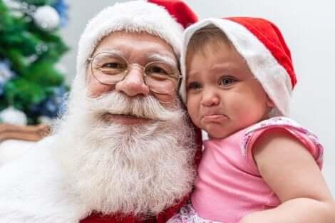 Un bébé qui pleure dans les bras du Père Noël.