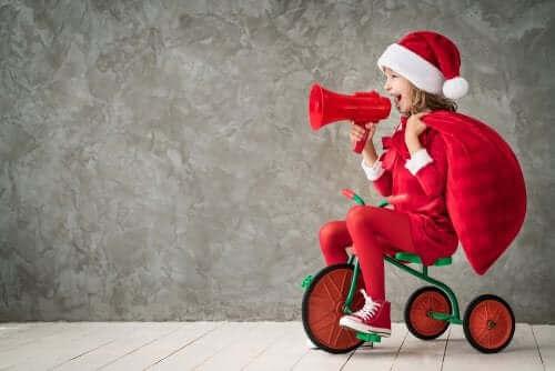 Une fillette sur un tricycle avec un chapeau de Noël.