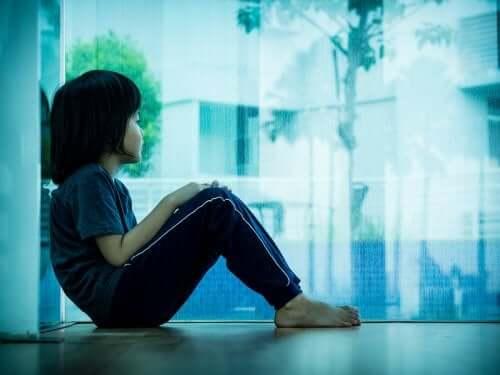 Un enfant seul regardant par la fenêtre