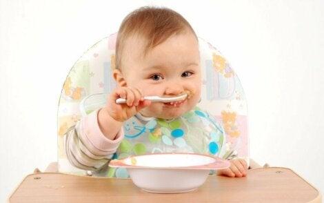 Un bébé en train de manger à la cuillère
