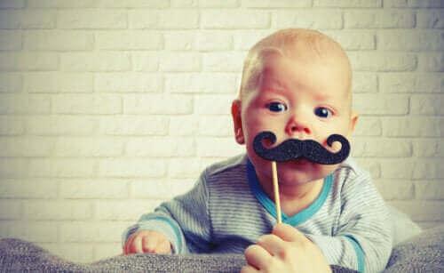 bébé tenant une fausse moustache