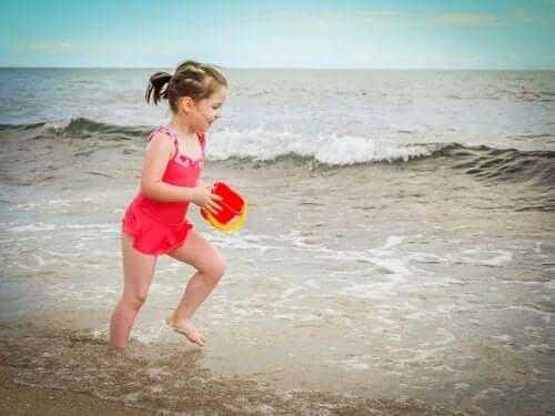 enfant à la plage avec un seau de sable