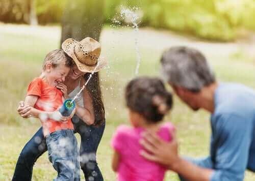 famille jouant avec un pistolet à eau à l'extérieur