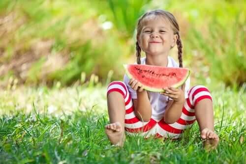 Une petite fille mange une pastèque