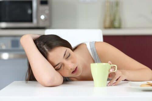 Une jeune fille dormant devant sa tasse de café