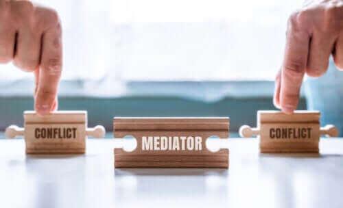 figurines en bois représentant la médiation d'un conflit