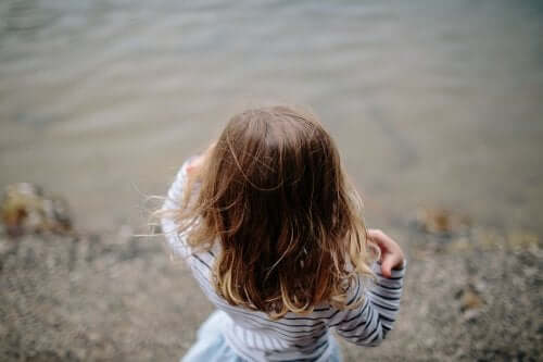 enfant au bord de l'eau avec cheveux détachés