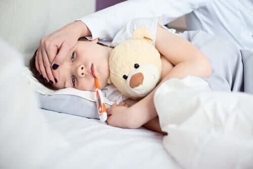 Un jeune garçon au lit, avec un thermomètre dans la bouche.
