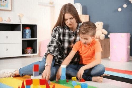 Un enfant autiste joue aux cubes avec sa maman