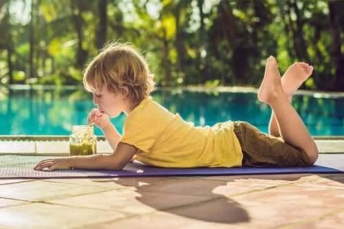 enfant buvant un smoothie près de la piscine