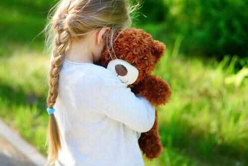 Une fille tenant son ours en peluche