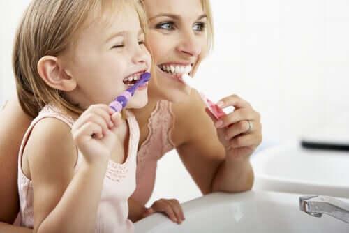 Une mère et sa fille se brossant les dents.