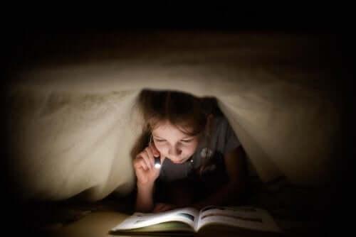 Un enfant qui lit sous sa couette.