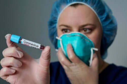 médecin tenant une fiole de sang infecté par le coronavirus