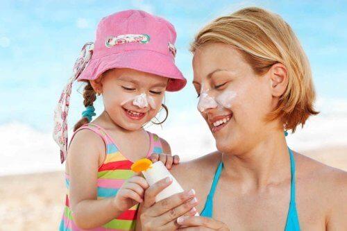 mère et fille mettant de la crème solaire
