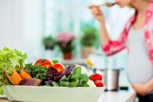 Une femme enceinte mange une salade contenant des légumes