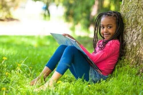 enfant lisant une BD adossée contre un arbre