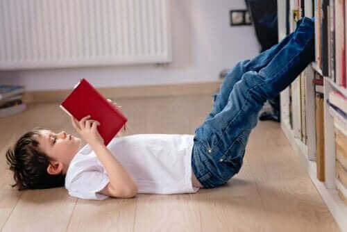 enfant lisant un livre assis par terre pendant le confinement