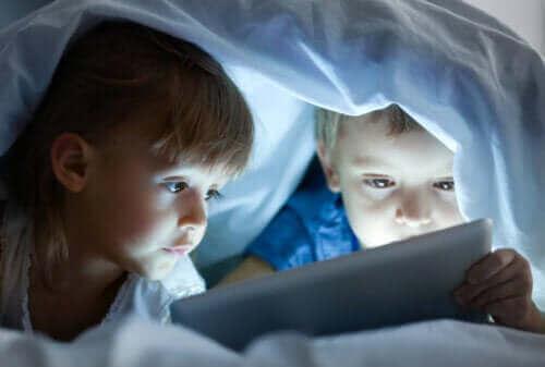 deux enfants regardant un film sur une tablette sous la couverture