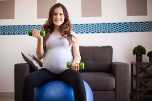 femme enceinte sur une fitball avec des haltères