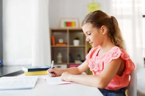 Une fille qui fait ses devoirs sur le bureau