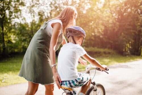 mère apprenant à faire du vélo à son fils