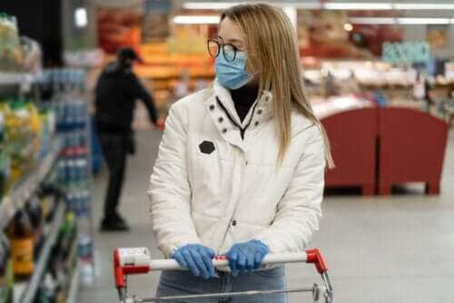 Une femme portant un masque et des gants en train de faire ses courses
