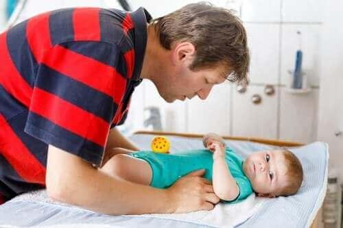 Un père changeant la couche de son bébé